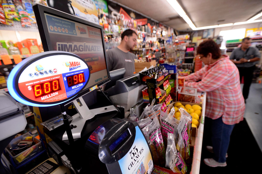 """. Gloria Ybarra, of Fontana, buys a Powerball ticket at Quicker Liquor along Sierra Avenue in Fontana May 17, 2013.  \""""Six hundred million dollars is a lot of money,\"""" said Quciker Liquor Store Manager Essa Mubarakah, says about the Powerball Lottery.  Nearly 40 people have purchased tickets by mid-day at the Fontana store.  The store displays past winning tickets at the lottery display. \""""We put them up for everybody to see ,\"""" says Mubarakah, \""""so they can know that they have a chance to win here. Its a lucky store.\""""  The Powerball Lottery, which California just joined earlier this year, is at $600 million for Saturday\'s drawing.  It is the third-highest jackpot in U.S. history.  GABRIEL LUIS ACOSTA/STAFF PHOTOGRAPHER."""