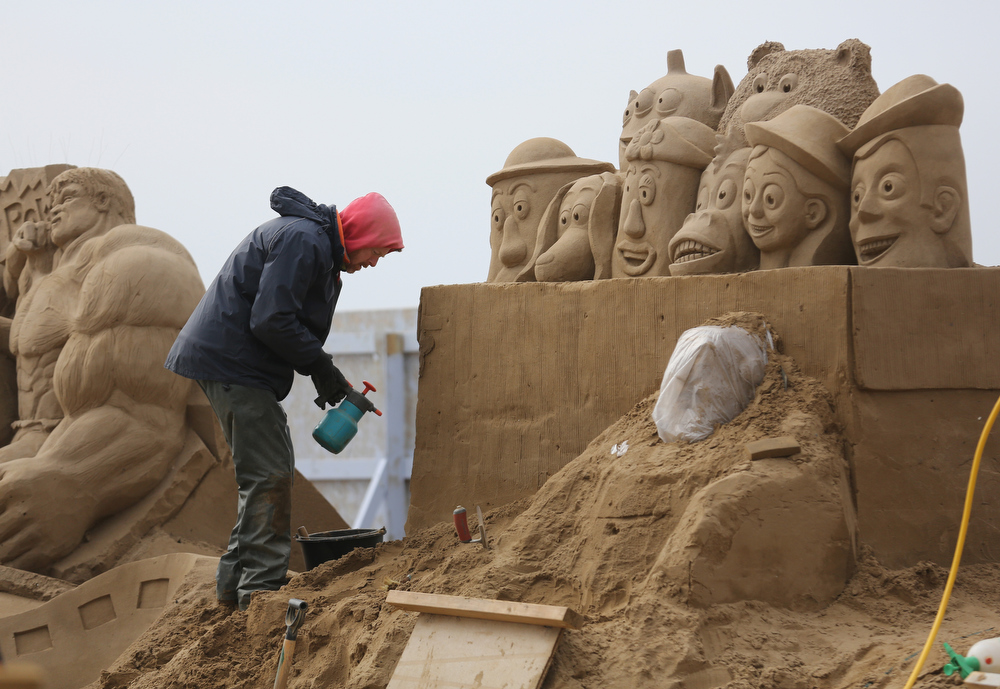 Description of . A sand sculptor works on a Toy Story themed sand sculpture as pieces are prepared as part of this year's Hollywood themed annual Weston-super-Mare Sand Sculpture festival on March 26, 2013 in Weston-Super-Mare, England. Due to open on Good Friday, currently twenty award winning sand sculptors from across the globe are working to create sand sculptures including Harry Potter, Marilyn Monroe and characters from the Star Wars films as part of the town's very own movie themed festival on the beach.  (Photo by Matt Cardy/Getty Images)