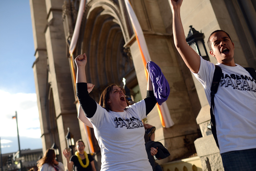 . DENVER, CO. - MARCH 13: Lindsay Peters, left, and Alex Lambis celebrate election of the new pope with a march from Civic Center to the Cathedral Basilica of the Immaculate Conception. Jorge Bergoglio of Argentina was elected pope. March 13, 2013. Denver, Colorado. (Photo By Hyoung Chang/The Denver Post)
