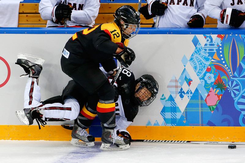 . Susann Gotz of Germany and Tomoko Sakagami of Japan collide against the boards during the first period of the 2014 Winter Olympics women\'s ice hockey game at Shayba Arena, Tuesday, Feb. 18, 2014, in Sochi, Russia. (AP Photo/Petr David Josek)