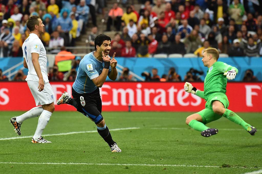 . Uruguay\'s forward Luis Suarez (C) celebrates scores past England\'s goalkeeper Joe Hart (R) as England\'s defender Phil Jagielka (L) looks on during the Group D football match between Uruguay and England at the Corinthians Arena in Sao Paulo on June 19, 2014, during the 2014 FIFA World Cup. BEN STANSALL/AFP/Getty Images