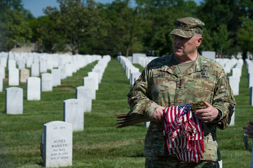 . Army Chief of Staff Gen. Mark Alexander Milley places flags at gravesite as the Army 3d U.S. Infantry Regiment, The Old Guard, honor the nation\'s fallen military heroes during its annual Flags In ceremony at Arlington National Cemetery, Thursday, May 24, 2018, in Arlington, Va. (AP Photo/Cliff Owen)