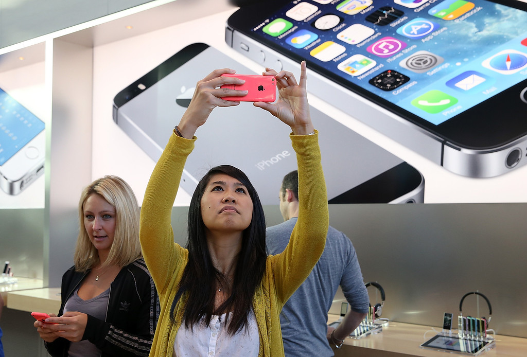 . Wendy Sudsinsunthorn takes a picture with the new Apple iPhone 5C at an Apple Store on September 20, 2013 in Palo Alto, California.  (Photo by Justin Sullivan/Getty Images)