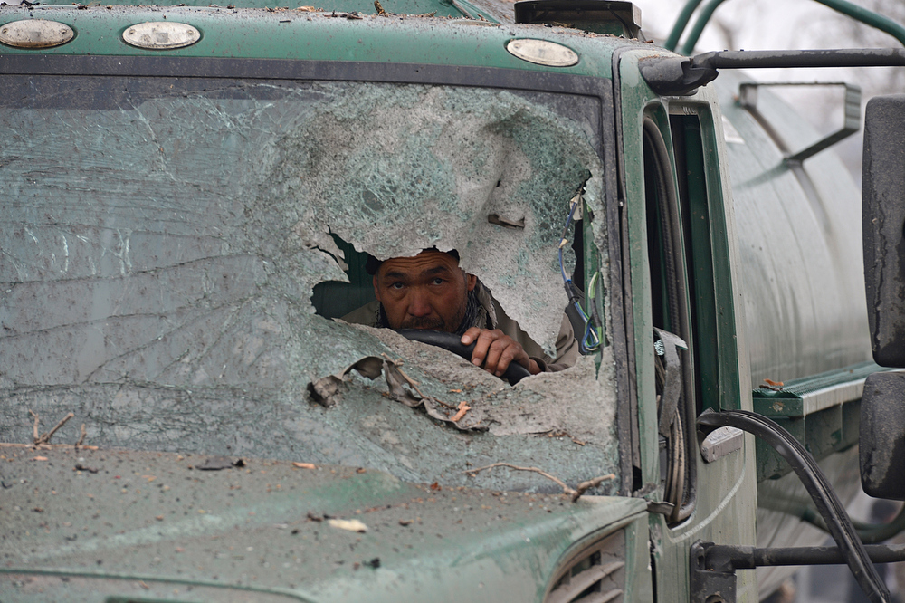 Description of . An Afghan truck driver peers through the broken windshield of his vehicle at the site of a suicide attack near the Afghan intelligence agency headquarters in Kabul on January 16, 2013. A squad of suicide bombers attacked the national intelligence agency headquarters in heavily-fortified central Kabul on January 16, killing at least two guards and wounding dozens of civilians, officials said.  SHAH MARAI/AFP/Getty Images
