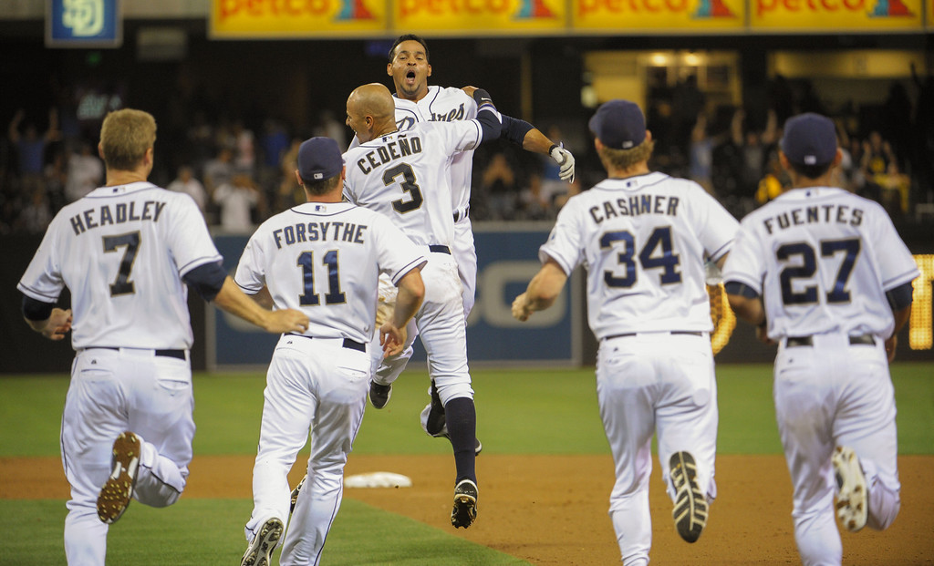. SAN DIEGO, CA - SEPTEMBER 6:  Jesus Guzman #15 of the San Diego Padres, center, celebrates with Ronny Cedeno #3 after he hit a walk-off single during the ninth inning of a baseball game against the Colorado Rockies at Petco Park on September 6, 2013 in San Diego, California.  The Padres won 4-3. (Photo by Denis Poroy/Getty Images)