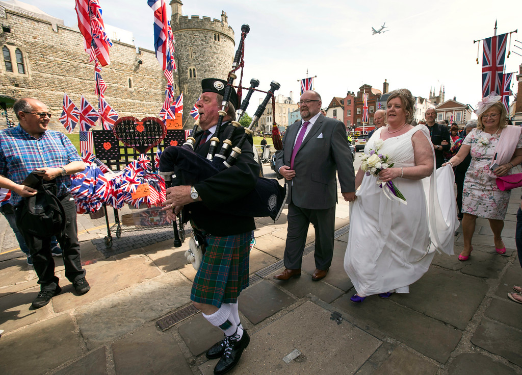. A bagpiper leads the procession for a newly wed couple as they pass in front of Windsor castle, England, Friday, May 18, 2018. Preparations continue in Windsor ahead of the royal wedding of Britain\'s Prince Harry and Meghan Markle Saturday May 19. (AP Photo/Peter Dejong)