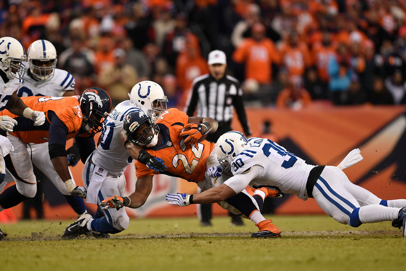. C.J. Anderson (22) of the Denver Broncos is tackled by LaRon Landry (30) of the Indianapolis Colts and Jerrell Freeman (50) of the Indianapolis Colts after a 6-yard gain in the second quarter. The Denver Broncos played the Indianapolis Colts in an AFC divisional playoff game at Sports Authority Field at Mile High in Denver on January 11, 2015. (Photo by AAron Ontiveroz/The Denver Post)