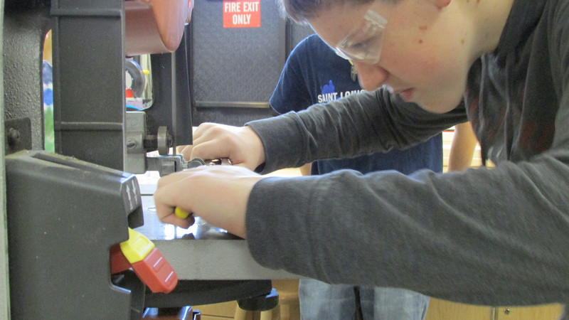 Nathan safely uses pliers to cut a small piece.