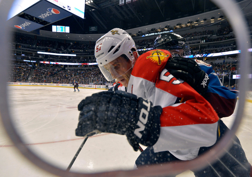 . Florida Panthers center Marcel Goc (57), from Germany, and Colorado Avalanche center John Mitchell (7) chase a puck into the corner during the third period of an NHL hockey game on Saturday, Nov. 16, 2013, in Denver. (AP Photo/Jack Dempsey)