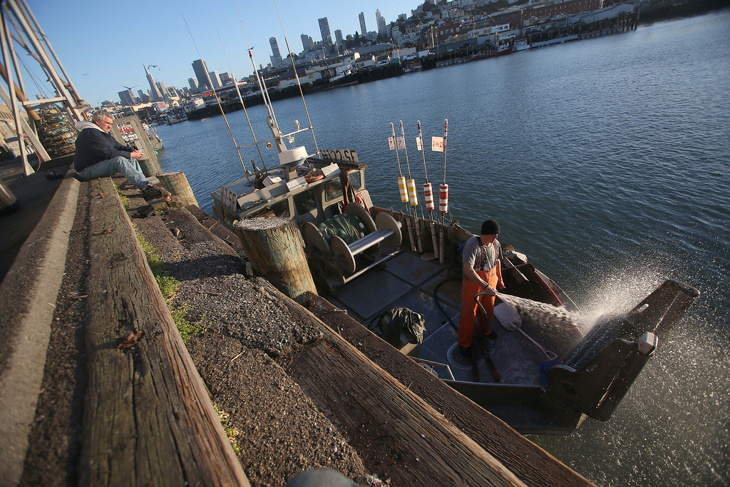 . Dennis Deaver\'s boat is hosed down after they unloaded 18-tons of herring at the San Francisco Community Fishing Association dock on Pier 45 in San Francisco, Calif., on Friday, Feb. 8, 2013.  (Jane Tyska/Staff)