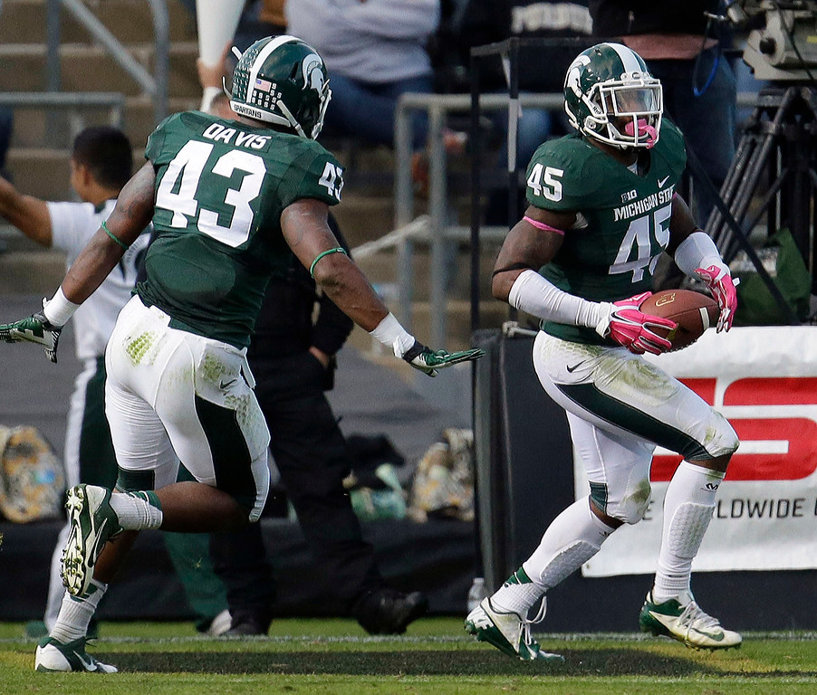 . Michigan State linebacker Darien Harris (45) runs through the end zone after intercepting a pass and running it in for a touchdown in the fourth quarter of an NCAA college football game against Purdue in West Lafayette, Ind., Saturday, Oct. 11, 2014. Michigan State won 45-31. (AP Photo/AJ Mast)