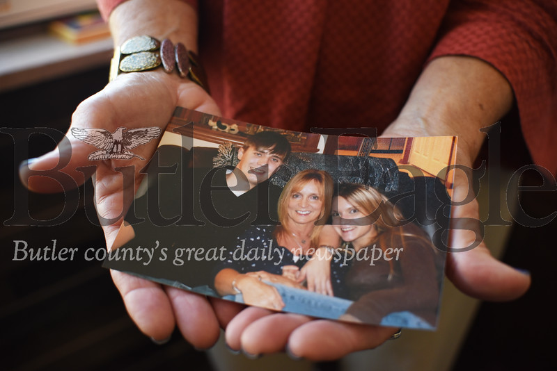 Tracy Hack holds a photo of herself, center, and two of her children, Ross and Melissa. Both children struggle with addiction. Tanner Cole/Butler Eagle