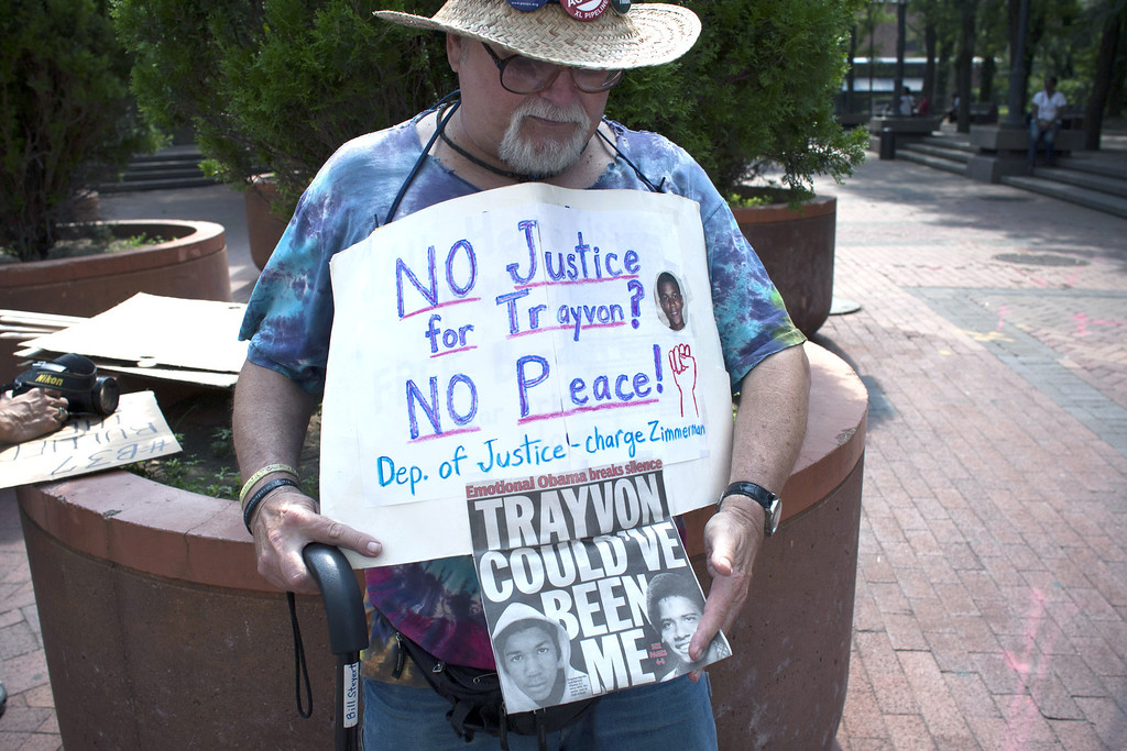 . NEW YORK, NY - JULY 20: A man holds a banner before a rally honoring Trayvon Martin outside One Police Plaza in Manhattan on July 20, 2013 in New York City.  Demonstrators have gathered in various cities across the country to protest the acquittal of neighborhood watchman George Zimmerman and press for his federal prosecution in the shooting death of teenager Trayvon Martin.  (Photo by Kena Betancur/Getty Images)