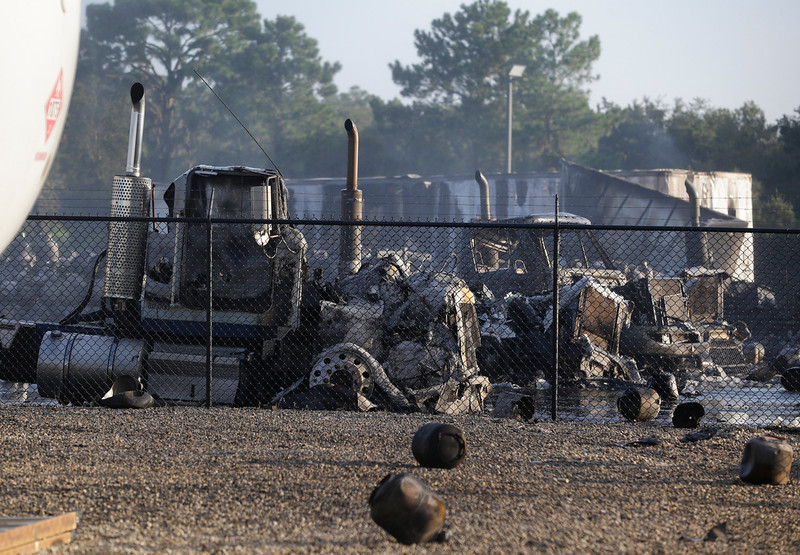 . The remains of several burned and melted trucks are seen after an explosion at a propane gas company Tuesday, July 30, 2013, in Tavares, Fla. In the foreground are several propane cylinders that exploded and landed in an area near the trucks. Eight people were injured, with at least three in critical condition. John Herrell of the Lake County Sheriff\'s Office said early Tuesday there were no fatalities despite massive blasts that ripped through the Blue Rhino propane plant late Monday night. (AP Photo/John Raoux)