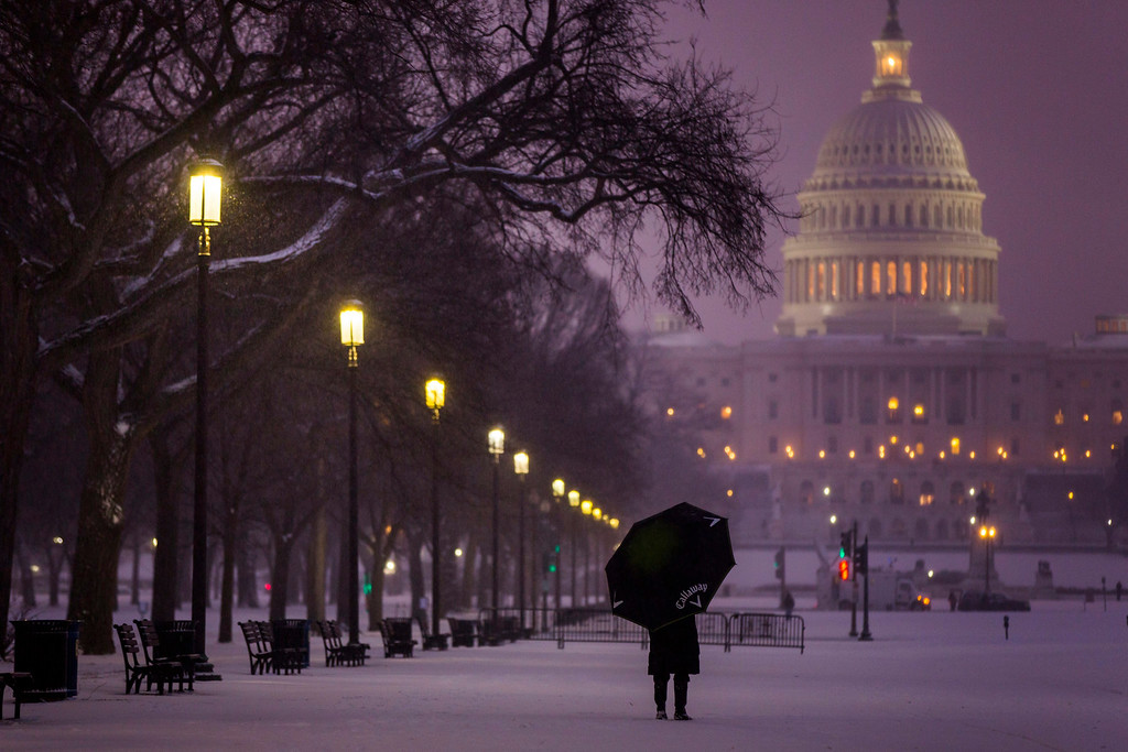 . A visitor to the National Mall pauses to look at a late afternoon snowfall in Washington, DC, USA, 21 January 2014. A blizzard has hit much of the US East Coast with snow accumulation expected to top seven inches (17 cm) in the nation\'s capital.  EPA/JIM LO SCALZO