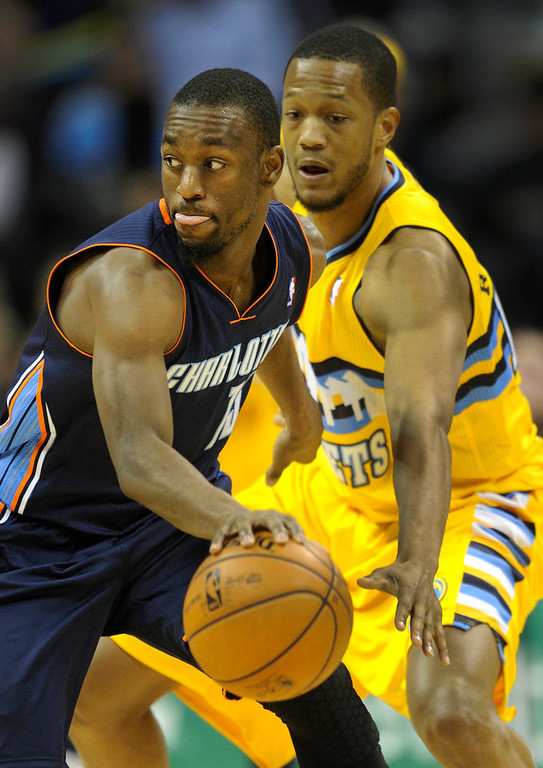 . Charlotte guard Kemba Walker, left, looked for a way past Denver forward Anthony Randolph, right, in the second half. The Denver Nuggets defeated the Charlotte Bobcats 110-88 at the Pepsi Center Saturday night, December 22, 2012.  Karl Gehring/The Denver Post