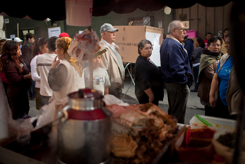 "On election day, voters in one of Mexico City's poorer neighborhoods line up outside waiting to cast their ballots. The busy streets of Mexico City provide no respite from the constant bombardment of vendors hawking everything from cell phone cases to street food, in this case some ""cabeza,"" or beef head tacos."