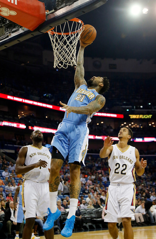 . Denver Nuggets small forward Wilson Chandler (21) goes to the basket as New Orleans Pelicans small forward Tyreke Evans (1) and point guard Brian Roberts (22) watch in the first half of an NBA basketball game in New Orleans, Sunday, March 9, 2014. (AP Photo/Bill Haber)