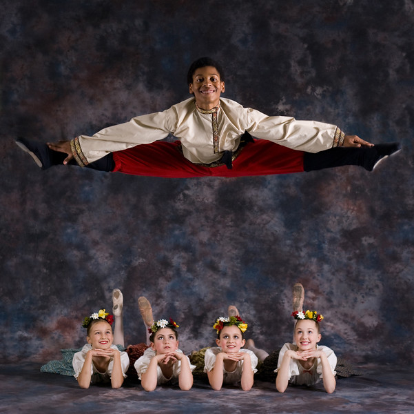 From Artur Sultanov's Russian Ballet Academy.  Produced in the studio.  Many people have inquired if this was actually photographed this way or if it was photoshopped.  Answer:  Yes, he actually jumped for the shot and was really in the air in this position above the girls, not photoshopped into place.