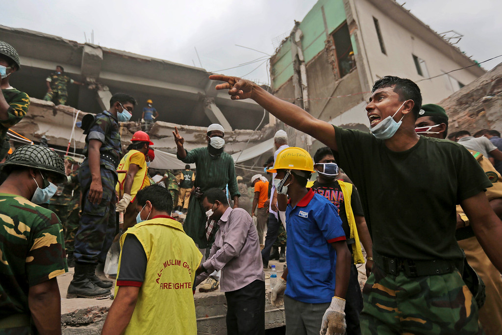 . A Bangladeshi rescue worker directs others as they search in the rubble of a building that collapsed Wednesday in Savar, near Dhaka, Bangladesh, Saturday, April 27, 2013. Police in Bangladesh arrested two owners of a garment factory in a shoddily-constructed building that collapsed this week, killing at least 324 people, as protests spread to a second city Saturday with hundreds of people throwing stones and setting fire to vehicles. (AP Photo/Kevin Frayer)