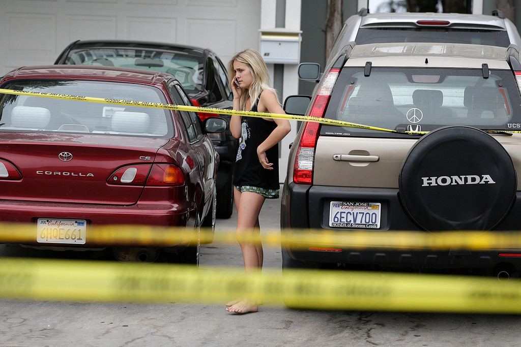 . A college student talks on the phone near the scene of a shooting on Saturday, May 24, 2014, in Isla Vista, Calif. A drive-by shooter went on a rampage near a Santa Barbara university campus that left seven people dead, including the attacker, and others wounded, authorities said Saturday. (AP Photo/Jae C. Hong)