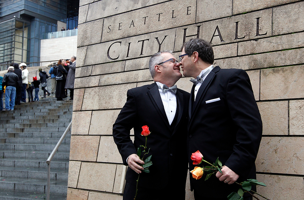 . Terry Gilbert, left, kisses his husband Paul Beppler after their wedding at Seattle City Hall, becoming among the first gay couples to legally wed in the state, Sunday, Dec. 9, 2012. Gov. Chris Gregoire signed a voter-approved law legalizing gay marriage Dec. 5 and weddings for gay and lesbian couples began in Washington on Sunday, following the three-day waiting period after marriage licenses were issued earlier in the week. (AP Photo/Elaine Thompson)