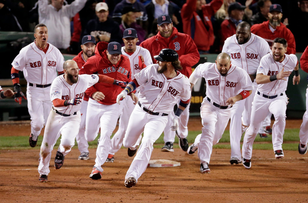 . Boston Red Sox players run aftar Jarrod Saltalamacchia after Saltalamacchia hits the game winning single during Game 2 of the American League baseball championship series against the Detroit Tigers Sunday, Oct. 13, 2013, in Boston. The Red Sox won 6-5. (AP Photo/Charlie Riedel)