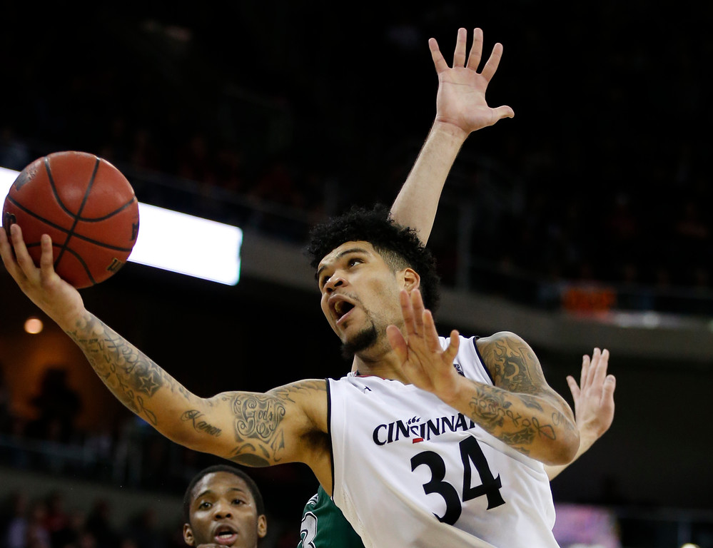 . Cincinnati guard Jarron Cumberland (34) shoots be;hind Cleveland State guard Dontel Highsmith, middle, obscured, during the second half of an NCAA college basketball game Thursday, Dec. 21, 2017, in Highland Heights, Ky. Cincinnati won 81-62. (AP Photo/Gary Landers)