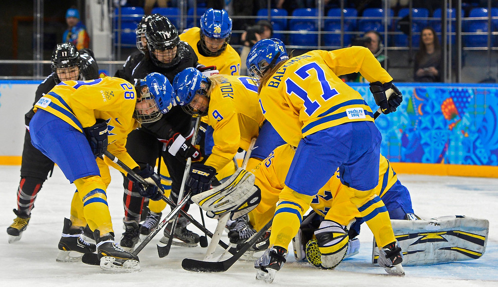 . Players from Sweden and Japan fight for the puck in the second period during the match between Sweden and Japan at the Shayba Arena in the Ice Hockey tournament at the Sochi 2014 Olympic Games, Sochi, Russia, 09 February 2014  EPA/LARRY W. SMITH
