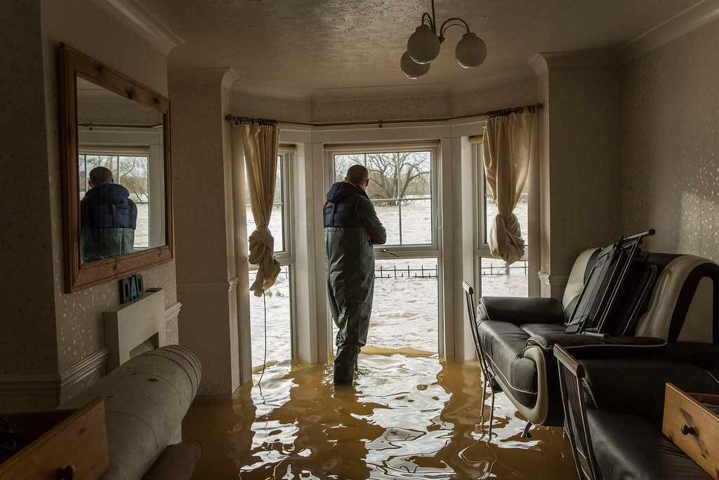 . Matt Beesley looks out of the window in his flooded living room that faces onto the River Severn on February 12, 2014 in Worcester, England. The Environment Agency has issued flood warnings for dozens of areas along the River Severn. With heavier rains forecast for the coming week people are preparing for the water levels to rise. (Photo by Rob Stothard/Getty Images)
