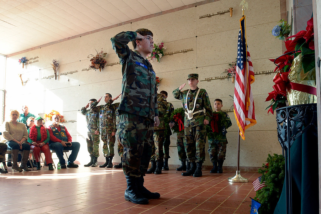 . Civil Air Patrol Cadet Evan Ellis salutes after laying his wreath on the memorial in the mausoleum at Sunset Memorial Park in honor of Wreaths Across America Day, Saturday, Dec. 13, 2014, in Nacogdoches, Texas. The program started in 1992 at Arlington National Cemetery in Virginia and has spread to almost 550 locations nationally to honor deceased veterans and service members listed as missing in action during the holiday season. (AP Photo/The Daily Sentinel, Andrew D. Brosig)