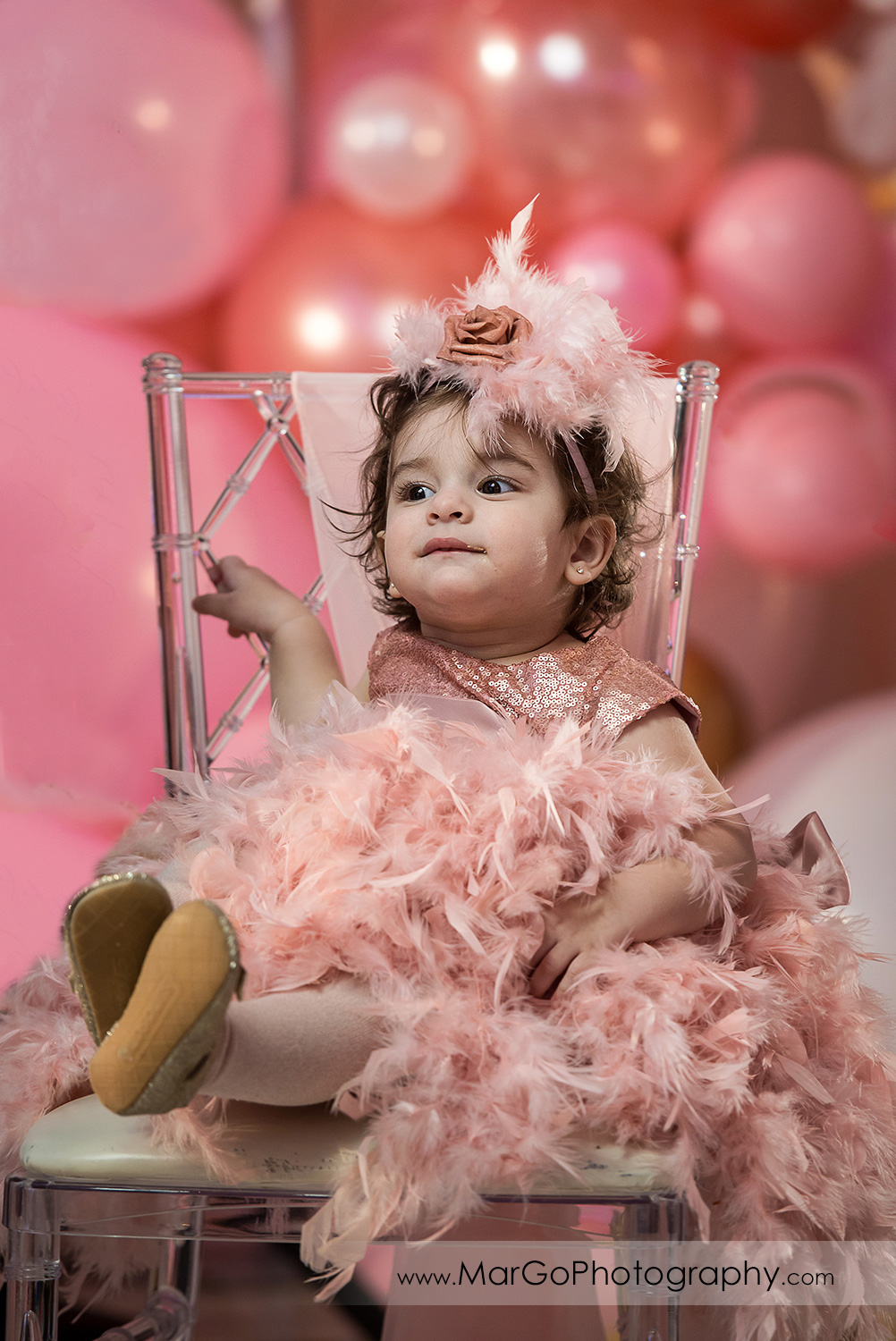 little girl in pink feather dress sitting on the chair at Newark Oasis Palace