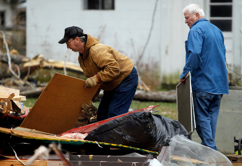 Description of . Barry Shanes, left, and Ronnie Shanes search through debris of a relatives home after a storm ripped through Coble, Tenn. early Wednesday, Jan. 30, 2013. A large storm system packing high winds, hail and at least one tornado tore across a wide swath of the South and Midwest on Wednesday, killing one person, blacking out power to thousands and damaging homes. (AP Photo/Butch Dill)