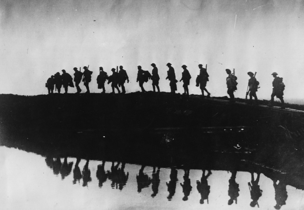 . 5th October 1917: Supporting troops of the 1st Australian Division walking on a duckboard track near Hooge, in the Ypres Sector. They form a silhouette against the sky as they pass towards the front line to relieve their comrades, whose attack the day before won Broodseinde Ridge and deepened the Australian advance. (Photo by Frank Hurley/Hulton Archive/Getty Images)