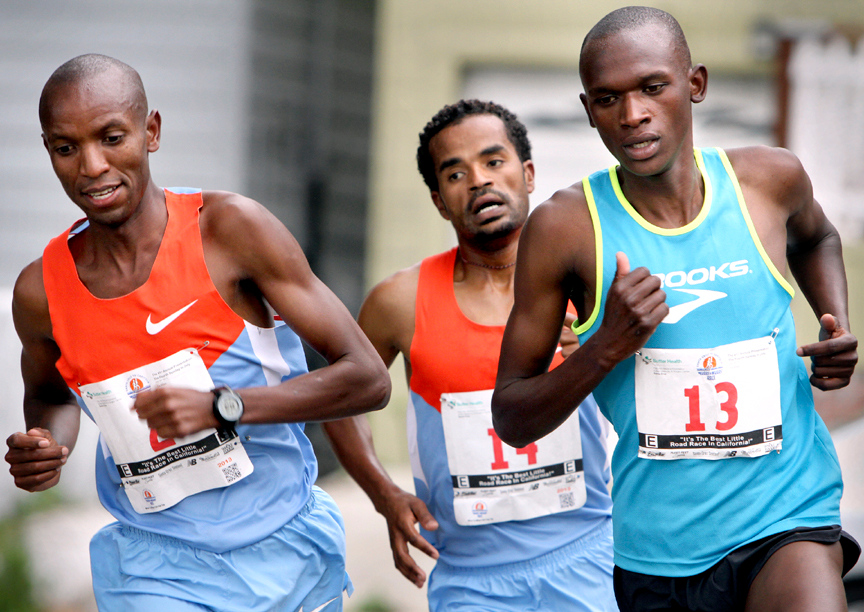 . The 2013 Wharf to Wharf winner Nelson Oyugi of Kenya, right, pulls ahead of Ashalew Maketa Neguse and Shadrack Kosegi as the pack of elite runners charge down East Cliff Drive in Santa Cruz on Sunday morning. Oyugi, 19, was running the annual race for the first time. (Kevin Johnson/Sentinel)