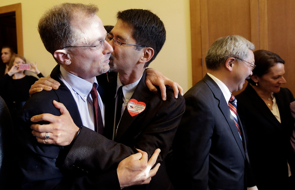 . John Lewis, left, gets a kiss from his partner Stuart Gaffney as they embrace after the Supreme Court cleared the way for same-sex marriage in California at the office of San Francisco Mayor Ed Lee at City Hall in San Francisco, Wednesday, June 26, 2013.  The justices issued two 5-4 rulings in their final session of the term. One decision wiped away part of a federal anti-gay marriage law that has kept legally married same-sex couples from receiving tax, health and pension benefits. The other was a technical legal ruling that said nothing at all about same-sex marriage, but left in place a trial court\'s declaration that California\'s Proposition 8 is unconstitutional.  (AP Photo/Jeff Chiu)