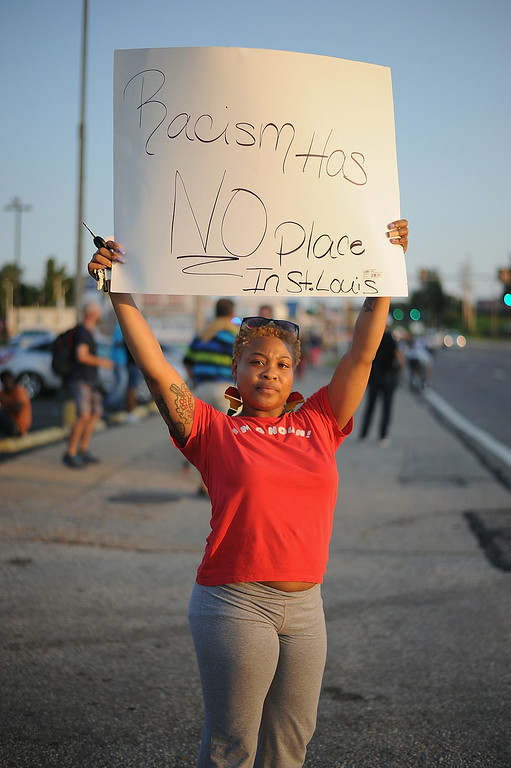 ". A protestor displays a sign during a peaceful protest on West Florissant Ave. in Ferguson, Missouri on August 19, 2014.  Police in the US city of St. Louis shot dead another suspect on Tuesday, a short distance from a suburb that is the scene of protests over the killing of an unarmed black teenager.  St. Louis Police Chief Sam Dotson said in a tweet that officers had responded to a call and found an apparently agitated man, armed with a knife who yelled ""kill me now\"" and approached the patrol. Michael B. Thomas/AFP/Getty Images"