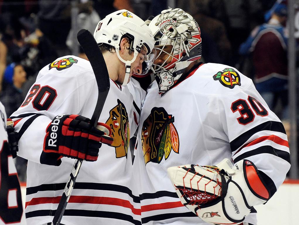 . Chicago Blackhawks goalie Ray Emery (30) celebrates a 5-2 victory over the Colorado Avalanche with Brandon Saad (20) during the third period of an NHL hockey game, Monday, March 18, 2013, in Denver. (AP Photo/Jack Dempsey)