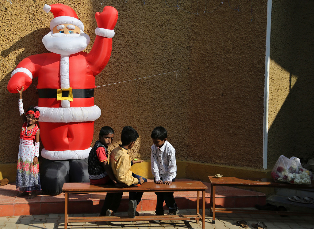 . Indian Christian children play next to an inflated figure of Santa after attending Christmas mass at \'Our Lady of Vailankanni\' Church, in Bangalore, India, Sunday, Dec. 25, 2016. Though the Hindus and Muslims comprise majority of the population in India, Christmas is a national holiday celebrated with much fanfare. (AP Photo/Aijaz Rahi)