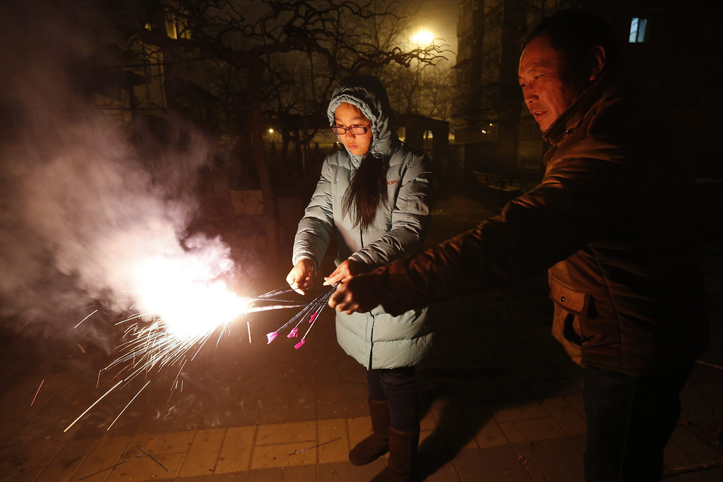 . Residents light sparklers outside their homes minutes after midnight in Beijing, China, 31 January 2014.   EPA/ROLEX DELA PENA