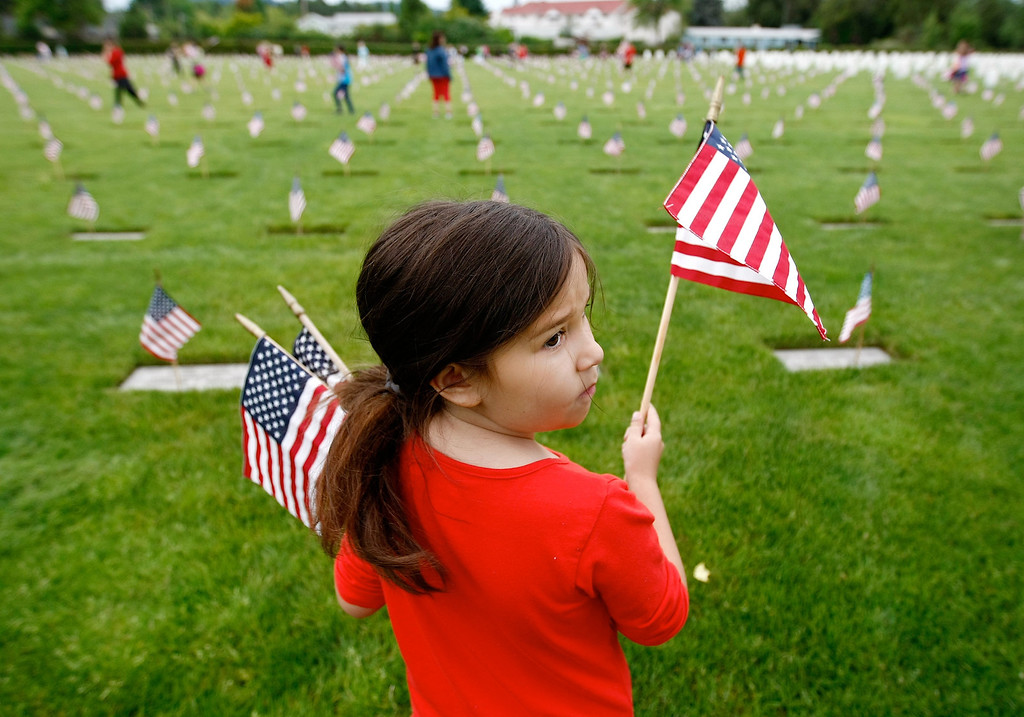 . In this May 23, 2014 photo, Fir Grove Elementary School third grader Skylee Blansett helps place flags at Roseburg National Cemetery in Roseburg, Ore. (AP Photos/The News-Review, Michael Sullivan)