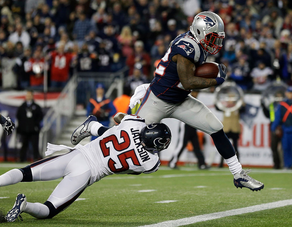 . Houston Texans cornerback Kareem Jackson (25) cannot restrain New England Patriots running back Stevan Ridley as he crosses the goal line for an eight-yard touchdown during the second half of an AFC divisional playoff NFL football game in Foxborough, Mass., Sunday, Jan. 13, 2013. (AP Photo/Elise Amendola)