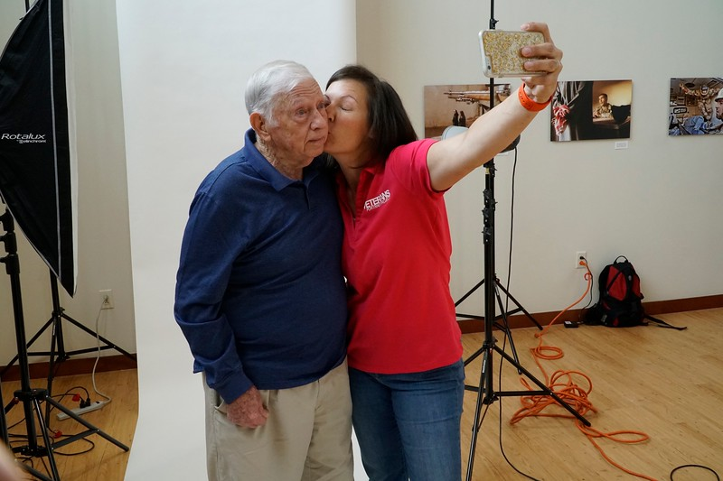 Stacy Pearsal takes a selfie and steals a kiss with WWII Veteran during her Veterans Portrait Project