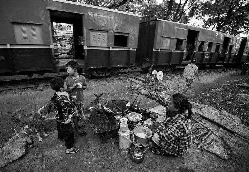 A family having breakfast on the street as a train drives past.  Meiktila, Myanmar, 2017.