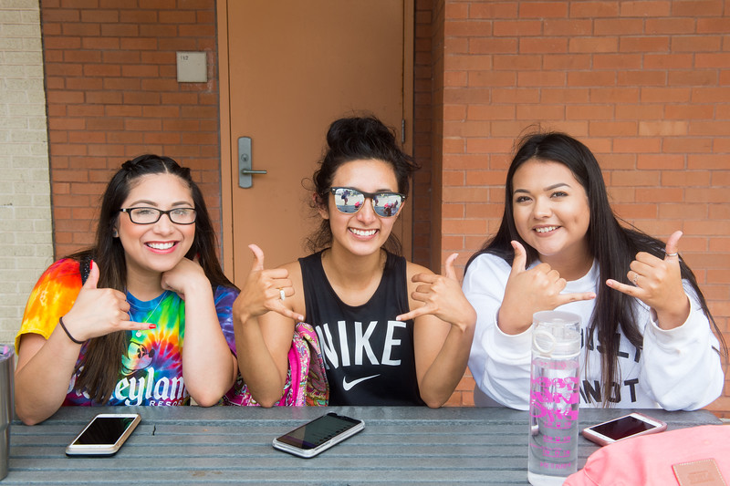 Chastity Pena (left), Laura Perez, and Anissa Gutierrez show their best shakas in the Center for Instruction courtyard.