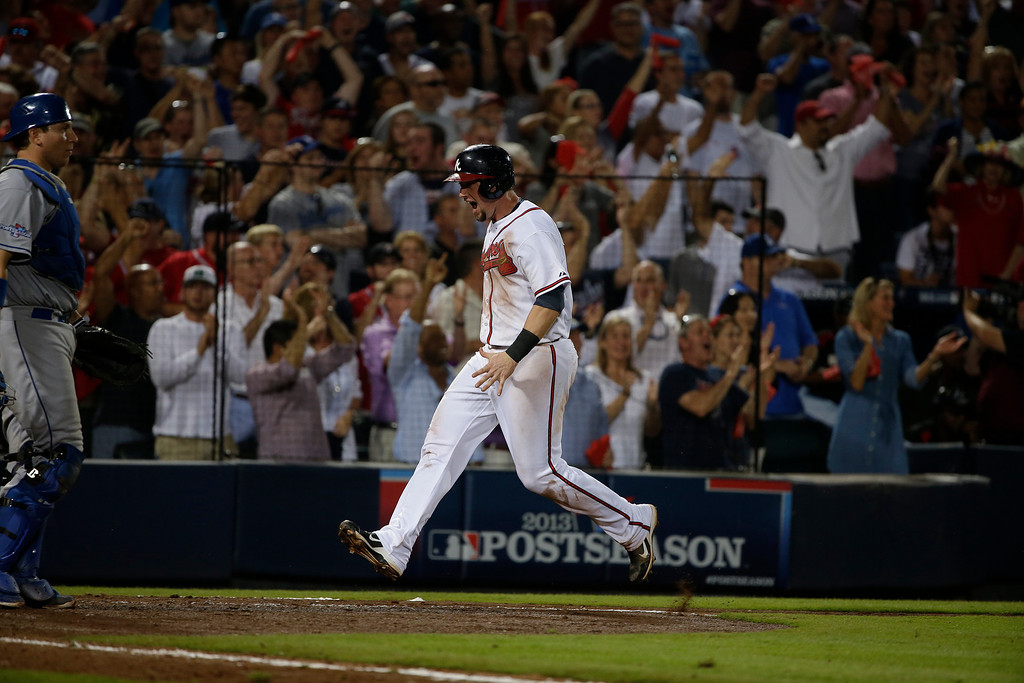 . Atlanta Braves third baseman Chris Johnson (23) celebrates after scoring on a Jason Heyward\'s  single in the seventh inning of Game 2 of the National League Divisional Series against the Los Angeles Dodgers, Friday, Oct. 4, 2013, in Atlanta. (AP Photo/John Bazemore)