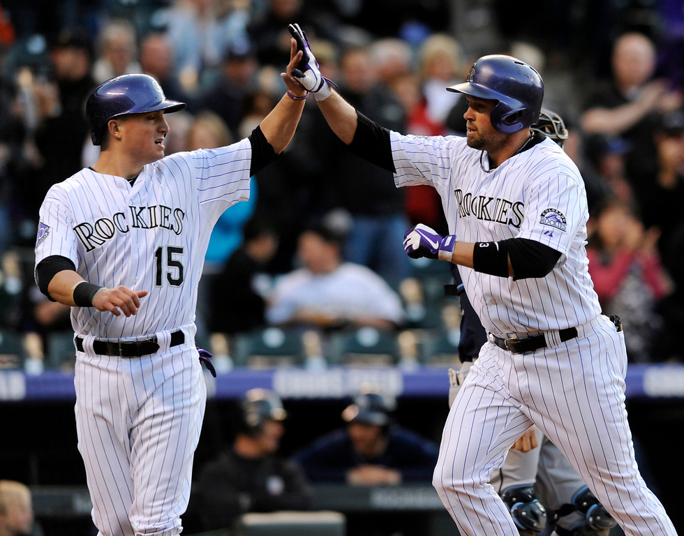 . Colorado Rockies\' Michael Cuddyer, right, celebrates a two-run home run hit off Tampa Bay Rays starting pitcher Matt Moore with teammate Jordan Pacheco (15) during the first inning of a baseball game on Friday, May 3, 2013, in Denver. (AP Photo/Jack Dempsey)