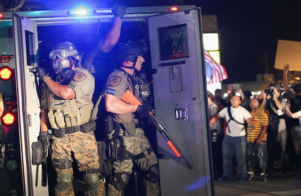 . FERGUSON, MO - AUGUST 18:  Police attempt to control demonstrators protesting the killing of teenager Michael Brown on August 18, 2014 in Ferguson, Missouri. Police shot smoke and tear gas to disperse the protestors with as they became unruly.  Brown was shot and killed by a Ferguson police officer on August 9. Despite the Brown family\'s continued call for peaceful demonstrations, violent protests have erupted nearly every night in Ferguson since his death.  (Photo by Scott Olson/Getty Images)