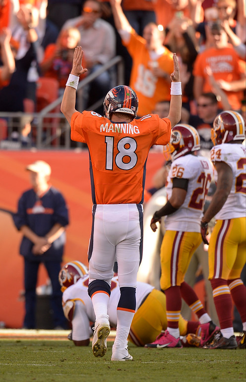 . Denver Broncos quarterback Peyton Manning (18) signals for a touchdown after Denver Broncos running back Montee Ball (28) ran it in during the third quarter. The Denver Broncos take on the Washington Redskins at Sports Authority Field at Mile High in Denver on October 27, 2013. (Photo by John Leyba/The Denver Post)