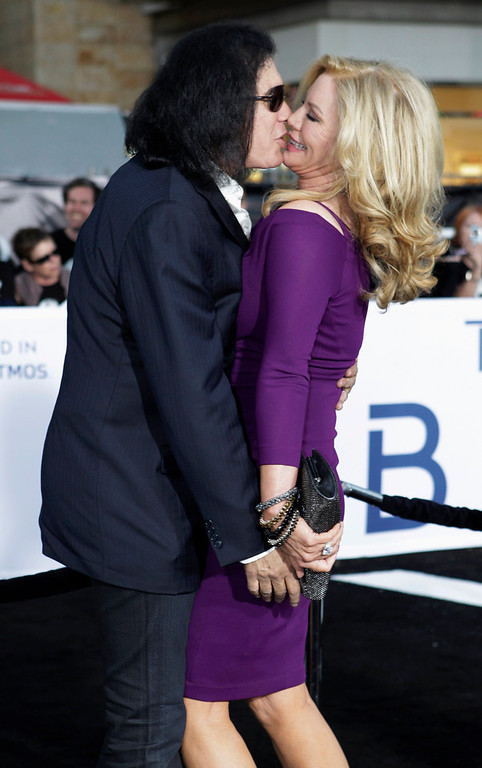 """. Musician Gene Simmons (L) kisses wife Shannon Tweed as they arrive as guests at the premiere of the new film \""""Oblivion\"""" in Hollywood, California April 10, 2013.  REUTERS/Fred Prouser"""